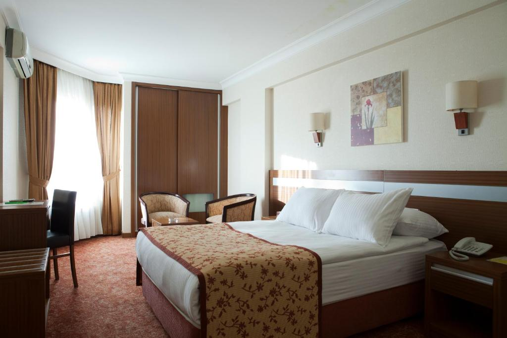 A bed or beds in a room at Atalay Hotel