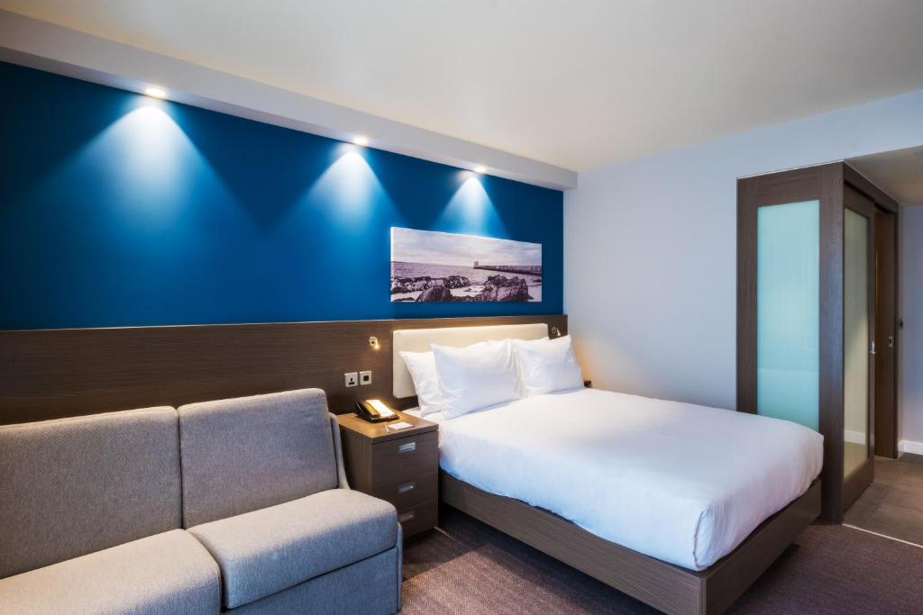 A bed or beds in a room at Hampton By Hilton Aberdeen Westhill