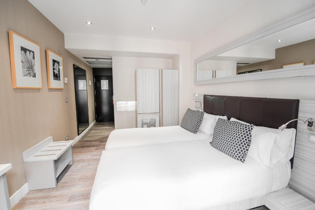 A bed or beds in a room at Petit Palace Puerta del Sol