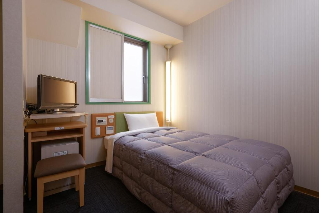 A bed or beds in a room at R&B Hotel Hakata Ekimae 1