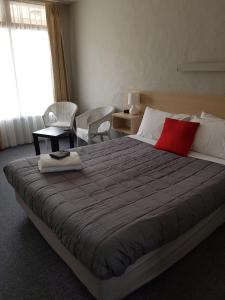 A bed or beds in a room at Belmore Motor Inn