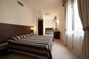 Un ou plusieurs lits dans un hébergement de l'établissement Hotel Margherita