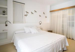 A bed or beds in a room at Hotel Es Marès
