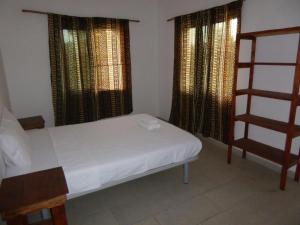 A bed or beds in a room at Sarawally Guesthouse