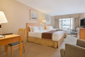 A bed or beds in a room at Ramada by Wyndham Nanaimo
