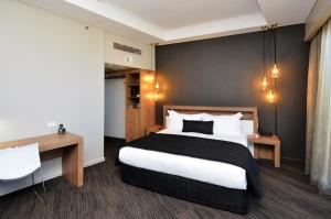 A bed or beds in a room at Hotel Grand Chancellor Townsville