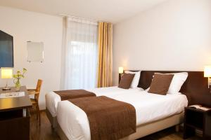 A bed or beds in a room at Séjours & Affaires Caen Le Clos Beaumois