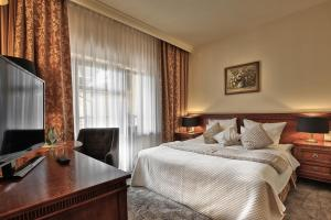 A bed or beds in a room at Grand Hotel Stamary