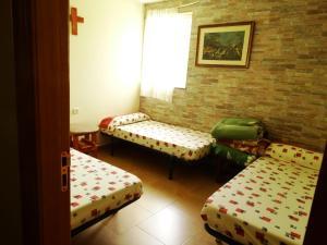 A bed or beds in a room at Albergue Peregrinos Santa Ana