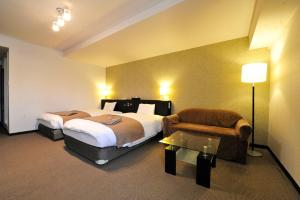 A bed or beds in a room at Hotel Royal Stay Sapporo