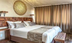 A bed or beds in a room at Sossusvlei Lodge