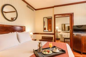 A bed or beds in a room at Eurostars Gran Hotel Santiago