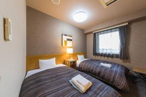 A bed or beds in a room at Route Inn Grantia Hanyu Spa Resort