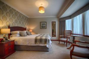 A bed or beds in a room at Strathburn Hotel