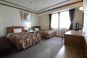 A bed or beds in a room at Neyagawa Trend Hotel