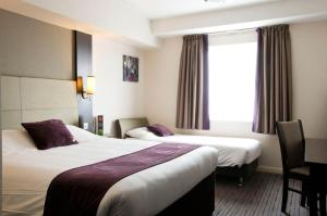 A bed or beds in a room at Premier Inn Heathrow Airport Terminal 4