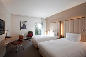 A bed or beds in a room at Hilton London Heathrow Airport Terminal 5