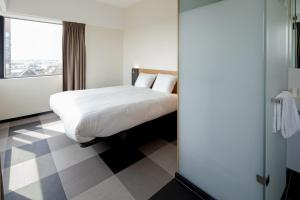 A bed or beds in a room at easyHotel Amsterdam Zaandam