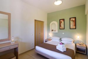 A bed or beds in a room at Pefkos Village Resort