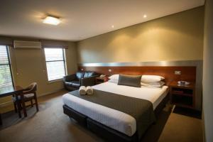 A bed or beds in a room at Seacombe House Motor Inn Port Fairy