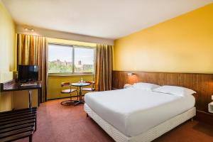 A bed or beds in a room at Hotel des Congrès