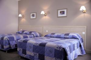 A bed or beds in a room at Hôtel du Cheval Rouge