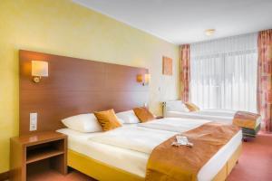 A bed or beds in a room at Novum Hotel Rega Stuttgart