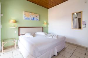 A bed or beds in a room at Pousada Farol do Itaguá