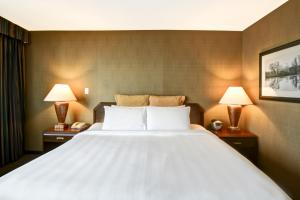 A bed or beds in a room at Chateau Lacombe Hotel