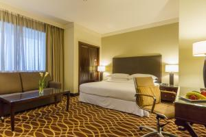 A bed or beds in a room at Grand Excelsior Hotel Deira