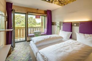 A bed or beds in a room at Explorer Hotel Berchtesgaden