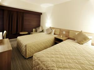 A bed or beds in a room at UNIZO INN Shin-Osaka
