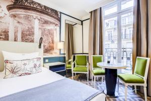A bed or beds in a room at Fraser Suites Le Claridge Champs-Elysées
