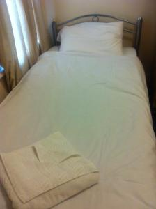 A bed or beds in a room at London Olympus Hotel