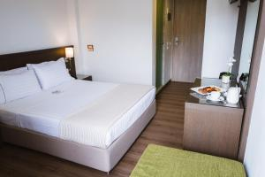A bed or beds in a room at Piraeus Port Hotel