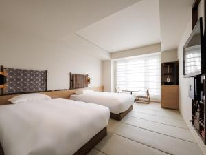 A bed or beds in a room at Kyoto Granbell Hotel