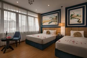 A bed or beds in a room at Hanoi Chic Boutique Hotel