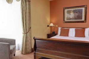 A bed or beds in a room at Best Western Plus Old Tollgate Hotel
