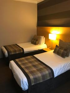 A bed or beds in a room at Buchan Hotel