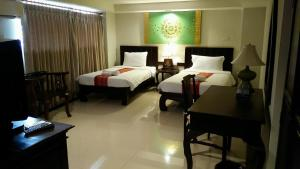 A bed or beds in a room at Swankaburi Boutique Hotel