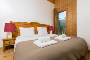 Un ou plusieurs lits dans un hébergement de l'établissement Madame Vacances Les Chalets d'Isola