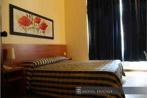 A bed or beds in a room at Hotel Ducale