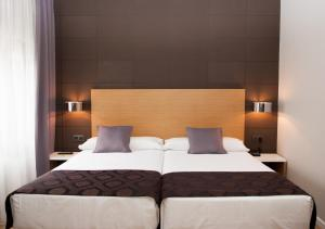 A bed or beds in a room at Hotel Universal