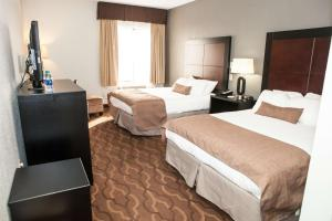 A bed or beds in a room at Best Western Commerce Inn