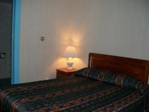 A bed or beds in a room at Mohican Motel