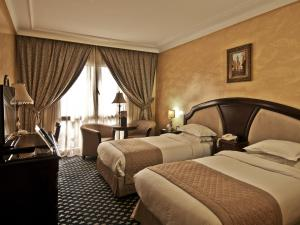 A bed or beds in a room at Ramada By Wyndham Fes
