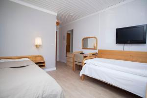 A bed or beds in a room at Stetind Hotel