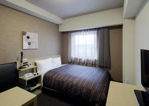 A bed or beds in a room at Hotel Route-Inn Ube