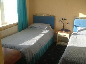 A bed or beds in a room at Tremains Guest House