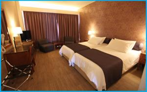 A bed or beds in a room at Poseidonia Beach Hotel